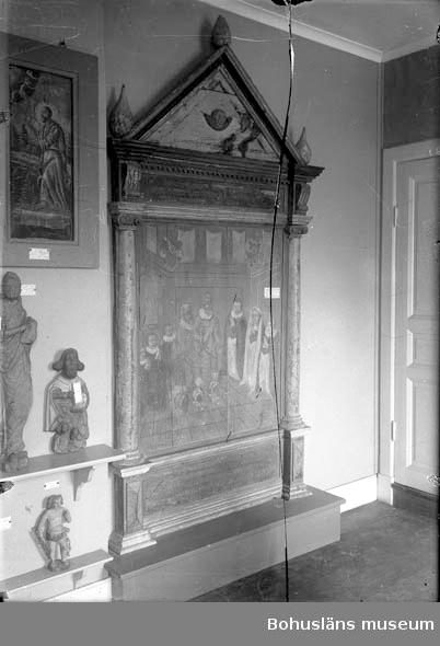 """Minnestavla, epitafium, målad på trä. Arkitektonsikt uppbyggd med kolonner på ömse sidor och med ett triangel-format fält (tympanon) upptill. Motivet visar två riddare i rustning samt tre gossar till vänster, och en äldre samt två yngre kvinnor till höger. Alla är knäböjande.  Bilden har följande text undertill: """"ERLIG WELBYRDIG MAND PEDER BAGGE TIL HOLMEGAARD SOM DÖDE DEN 8 FEBRUARI ANNO 1606 SAMMELEDIS HANS KIERE HUSFRUE ERLIG VELBYRDIG OC GUDFRÖGTIG FRUE FRU KARINNE PEDERSDAATER SOM DÖDE DEN 14 MARTI ANO 1578 MED BEGIS DER BÖRN GUD DERRIS SIELER HAFVE"""".  Över bilden står det: """"Denne Epitaphium hafwer grosshandlaren wälädle Herren herr Fridrich C Bundson på Holma Låtit Renovera Anno 1787. Epitafiet har ursprungligen hängt i Brastads gamla kyrka som revs 1876. Den ersattes med en ny kyrkobyggnad samma år.   Ur """"Förteckning över lösa föremål av historiskt eller konstnärligt värde som böra vara uppförda i kyrkans inventarieförteckning. Brastad kyrka, augusti 1918: Hanna Eggertz, fil. Kand. Tillhörigt Brastad gamla kyrka förvaras Uddevalla museum: Kyrkbänk 1670 Maria Magdalena och kvinnligt helgon, träskulpturer, omkr. 1500. Epitafium över Peder Bagge (+ 1606)""""  Ett epitafium är en minnestavla över döda personer. Epitafiet är sedan 1938 deponerat i Brastad kyrka, se brevväxling m a a ärendet i 238 Topografiska arkivet / Brastad kyrka. Se Placering.  Föremålsfotot är från Uddevalla museums kyrkliga utställning 1920, UMFA54467:0422. Se bilagor i Bilagepärmen.  Ur Nationalencyklopedien, Internetkälla 2009: Epita´fium (lat. epita´phium, av grek. epita´phios 'hörande till grav', 'hörande till begravning', av epi- och ta´phos 'grav', 'begravning'), epitaf, inskriftsförsedd minnestavla, uppsatt i kyrka i anslutning till en grav (jfr kenotaf). Epitafier blev vanliga i de protestantiska länderna under 1500- och 1600-talen. De gavs ofta en rik arkitektonisk gestaltning, besläktad med samtida predikstolar och altaruppsatser. Epitafier kan vara av trä, sten eller metall och uppta"""