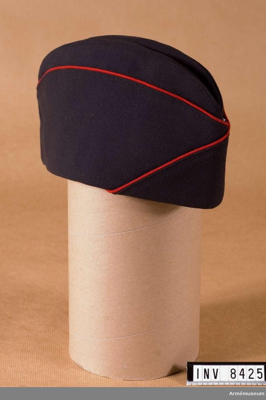 Av mörkt stålgrå ripsdiagonal med röd passpoal. Foder i svart bomullstyg som är stämplat SVEA 64 och kronstämpel. Svettrem i bomullstyg. Källa: UNIA 1977 bild 6:4. Även för Göta livgarde.