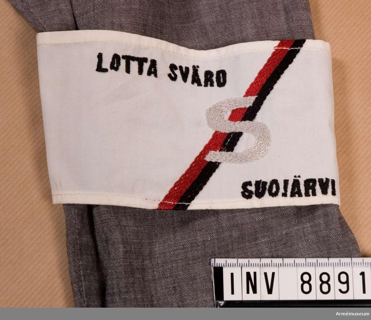 Längd 400 mm. Bredd 80 mm. Armbindel som ska sitta på vänster ärm på lottaklänningen Lotta Svärd. På snedden mitt på armbindeln en balk broderad i rött och svart silke. Mitt på balken ett broderat S i grått silke. På vänster sida därom vid övre kanten är det broderat med svart silke Lotta Svärd och nedtill på högra sidan Suojärvi som betecknar distriktet. S:et betecknar Sortala krets. Armbindeln är på insidan märkt med Sotamuseo nr 27650.2.  Samhörande nr är 8886 - 8894.