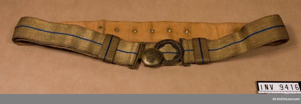 Paradskärp av bronsfärgad metalltråd med en 2 mm bred blå silkerand i mitten. Bärs av officer och underofficer till parad. Spännet är av bronsfärgad metall. Den inre rundeln (då skärpet är knäppt) bär tre kronor, två över den tredje. Den yttre rundeln i spännet bär stiliserade blad. Skärpet är reglerbart, och är försett med sölja för att fasthålla den överskjutande tampen. Öljetterade hål på avigsidan och en hake för olika lägen. Skärpet är skinnskott med ljust läder.