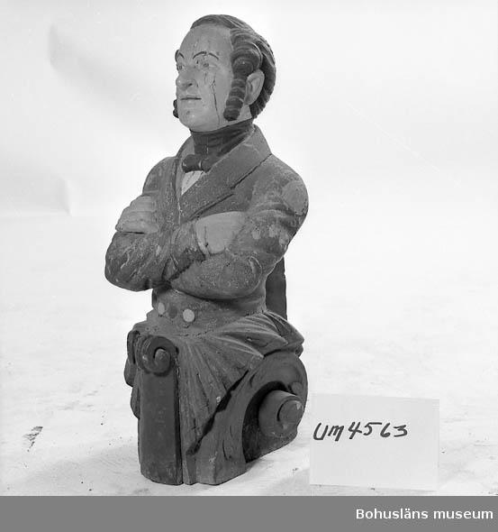 Föremålet visas i basutställningen Uddevalla genom tiderna, Bohusläns museum, Uddevalla.  Galjonsfigur. Man i halvfigur. Polykrom. Mörkt hår och långa polisonger, blå redingot, vit skjorta och svart halskrage och rosett (fluga). Färgen är mycket krackelerad och har fallit bort på vissa ställen. Användningstiden är uppskattad.  Ur handskrivna katalogen: Galionsbild H: 74. Galjonsbild. polykrom träfigur från Uddevallabarken Lord Palmerstone.