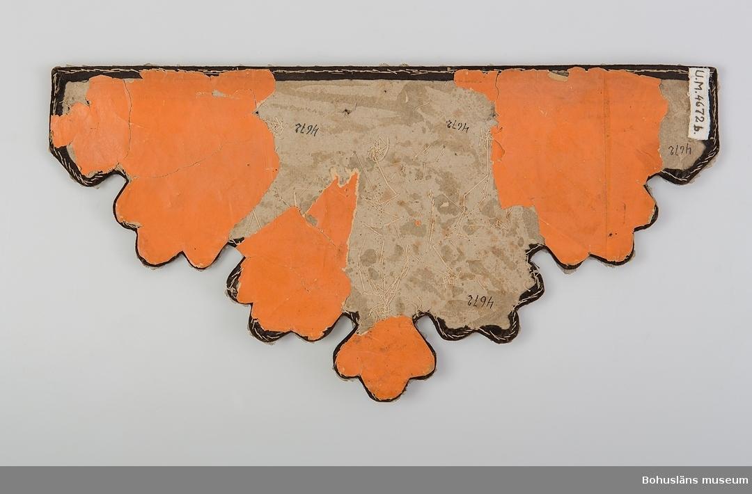 """Hyllbård med rak överkant och rundat taggig nederkant, bredast på mitten. Av brun sammet fastsydd vid en pappskiva. Dekorerad med  en blomsterbukett (nejlikor?) sydd av vita glaspärlor och (troligen)  fiskfjäll med ritsade mönsterlinjer. Ytterst längs kanterna en """"ram""""  av fiskfjäll(?). På baksidan är rödgult (orange) papper fastklistrat. Brunt som bottenfärg i broderier blev vanligt på 1870-talet, men mörka  färger förekom även några decennier tidigare. Naturalistiska blommor var vanliga sedan nyrokokon på 1840-talet och att använda nya blomsorter, framodlade i växthus, som broderimotiv blev allt vanligare  kring mitten av 1800-talet då storskalig växthusodling av olika, förr  mer sällsynta, blommor tog fart. (se litteraturen) Exakt när denna hyllremsa är ifrån är osäkert. Ett litet hål. Några ställen på """"ramen"""" skadad.  Litteratur: Fleming/Lindvall-Nordin m fl, Rosor och violer i korsstygn, LT Stockholm 1983, sid. 41-42.  Fredlund, Jane, Stora boken om livet förr, ICA-förlaget Västerås 1981, sid. 98-105.  Rosenknopp och yllestopp,  utställningskatalog från Helsingfors Stadsmuseum 1986.  Westerdahl,  Elisabeth, Pärlbroderade prydnader, ur Antik och auktion nr 4 1994. Se även bild på piphylla i Kulturen 1945 sid. 99.  Ur handskrivna katalogen 1957-1958: Två hylldukar, pärlor m m isydda b) 44 x 22 cm. Brun sammet m. pärlbroderier. Ngt söndrig i kanterna."""