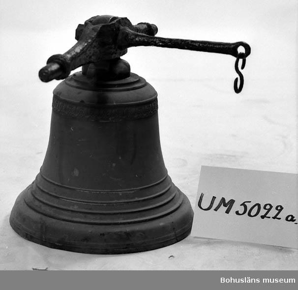 Ur handskrivna katalogen 1957-1958: Vällingklocka Klockan a) H. 42, D. 38 cm; m. axel och arm för klockrepet, av järn (klockan brons). Järnet rost. b) och c) lager f. axeln, mått: c:a 11 x 5 x 5 cm; m. isittande bultar. Rostiga.  Lappkatalog: 92
