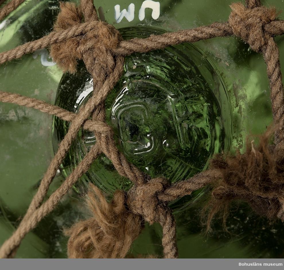 Grön kula. På proppen i puntelhålet är det inpressat P.C.F och ett liksidigt kors ovan och nedan C. Inflätad i bomullsnät. Nätet är söndrigt.