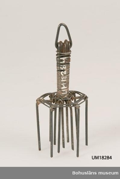 Upprättstående handtag av tätt virad ståltråd. Överst är en ståltråd tillböjd i en trekantsform för att hänga i. Elva piggar placerade i en ring sammanhållna av en tråd som bildar ett spindelvävsliknande mönster.  Se bilaga i Bilagepärmen.