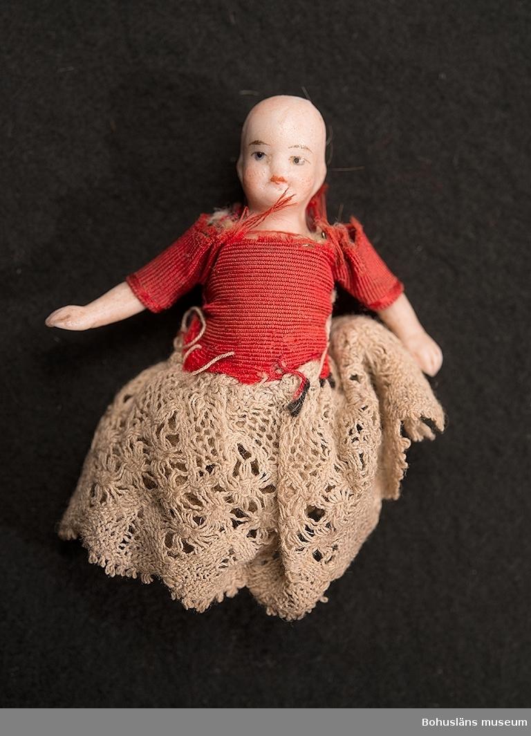 Liten docka i porslin med ledade ben och armar. Spetskjol och blus i röd ripssiden, virkad spetsunderkjol. Dockans ben är avbrutna. Dockskåpsdocka.
