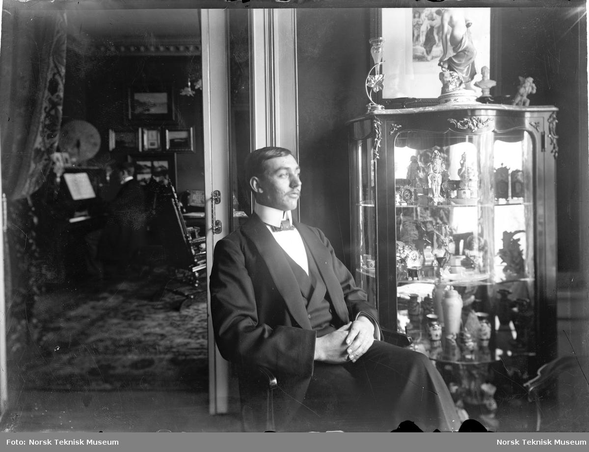 Mann sittende i stue foran vitrineskap. Mann som spiller piano i rommet bak.