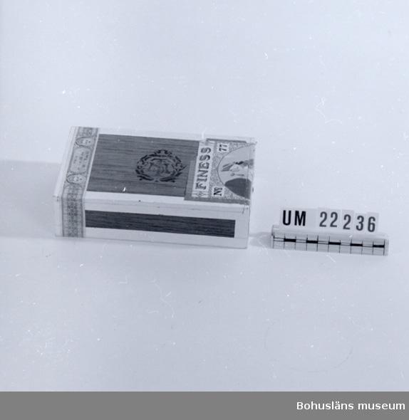 """594 Landskap BOHUSLÄN  Lådan märkt med text som följer: """"Finess No 77 A.-B. Svenska Tobaksmonopolet"""". Motiv: I halvcirkelform en man i rokokoklädsel med monokel i ena handen och käpp i den andra. Träd i bakgrunden. Färger: Rött, gult, vitt, mörkt olivgrönt samt beige. Angivet på pappersremsa klistrad på lådan: PRIS pr. 1 st. 15 öre, pr 50 st. 7.50 Kr. Lådan innehåller stjärnor av foliepapper; sekundär användning.  UMFF 93:3  Information hämtad i juni 2007 från www.tobakshistoria.com Finess, n:r 77 Tillverkas av: Svenska Tobaksmonopolet (STA efter 1962, senare Swedish Match) Cigarr tillverkad av Svenska Tobaksmonopolet: 1919-1934 1939-1940 1943-1944 Priset 1940 var 7,50 kr för låda á 50st. eller 1,50 kronor för ask om 10 st."""