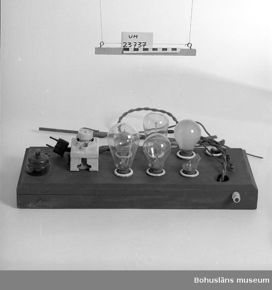 """471 Tillverkningstid 1920-1930 151 Sakord *EL AV 594 Landskap BOHUSLÄN  Tre sladdar med stavar av koppar (rör) total L: 160 cm samt sladd med elkontakt L: 49 cm. Rektangulär sockel av trä. Ovansidan 7 st lamphållare samt ström- brytare i svart och säkringshållare av vitt porslin med elpropp. 6 st glödlampor (1 av mjölkglas) en av lamporna trasig. En koppar- stav lös. Text på säkringshållaren: """"550 VOLT MAX"""" samt: """"500 VOLT MAXIMAL DR GM"""" på elproppshållare. Alla glödlamporna av olika form. På en text: """"SKADIA 220-25 W"""". Motståndet använt vid elektronisk försilvring och förgyllning."""