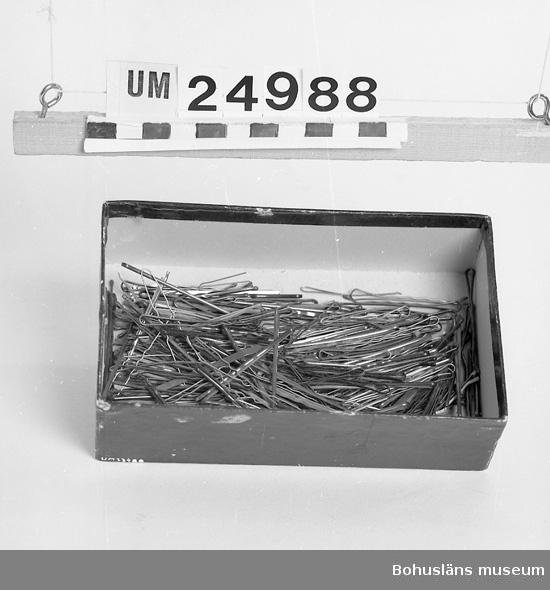 594 Landskap BOHUSLÄN  Mörkröd papplåda, sekundär, med hårnål. Lådan använd på damfriseringen.  På negativet står 24988. Föremål från Brorssons Damfrisering i Kungshamn, se UM023941.