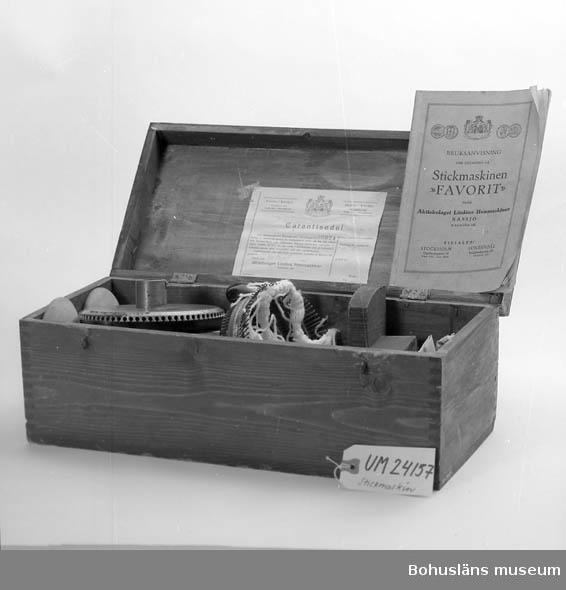 """Köpt på auktion efter David Andersson. Har troligen använts av hans syster - hon ägnade sig åt hemstickning. Lådan är betsade röd/brunt. Locket sitter fast med två gångjärn. Lådan stängs med två små krokar. På locket finns ett handtag av metall. På insidan locket finns en garantisedel utfärdad den 20 september 1920. Där står bl a att maskinen är avsynad av G.O och packad av H-d. Tillverkningsnummer: 6974.  Lådan innehåller 3 st tyngder, mejsel, långkrok, spännfjäder, kort krok, arbetskrork, 2 st spolar, 1 st lös nålbädd, 2 st vikta ark innehållandes nålar, en tändsticksask med nålar, 2 st vaxbitar inslagna i papper, 1 st korg, 1 st ledarskiva med nålbädd, ett tomt kuvert samt  häftet """"Bruksanvisning för stickning på Stickmaskinen """"FAVORIT"""" från Aktiebolaget Lindéns Hemmaskiner Nässjö Rikstelefon 162"""". Det fattas vissa delar jmrf med sid 77 - 78 i bruksanvisningen.   Det finns ett """"skruvjärn"""" som maskinen sätts fast med i bordsskivan. Det är inte en originaldel.  Uppgifter från Göran Andersson på Textilmuseet i Borås, maj 2005. Det finns flatstickningsmaskiner och rundstickningsmaskiner, eller flatstick och rundstick, som de kallas.  Rundsticken kallas också """"strumpekvarn"""" eftersom man """"mal runt"""" som med en kaffekvarn.  Med rundsticken görs främst strumpor, men man kan också sticka en rak slang som sedan klipps upp och förvandlas till olika plagg. Med flatsticken görs tröjor, mössor, strumpor och vantar. Det är lätt att sticka runda plagg också i flatsticken, då arbetar man i två plan - när man drar åt ena hållet blir det framsida, på tillbakavägen blir det baksida. Flatstickningsmaskiner var mycket vanligare, enligt Göran Andersson. 95 % av stickmaskinerna i hemmen var flata och 5 % runda. Största svenska tillverkaren var Per Persson, som startade 1894. Textilmuseet har 42 av hans maskiner!"""