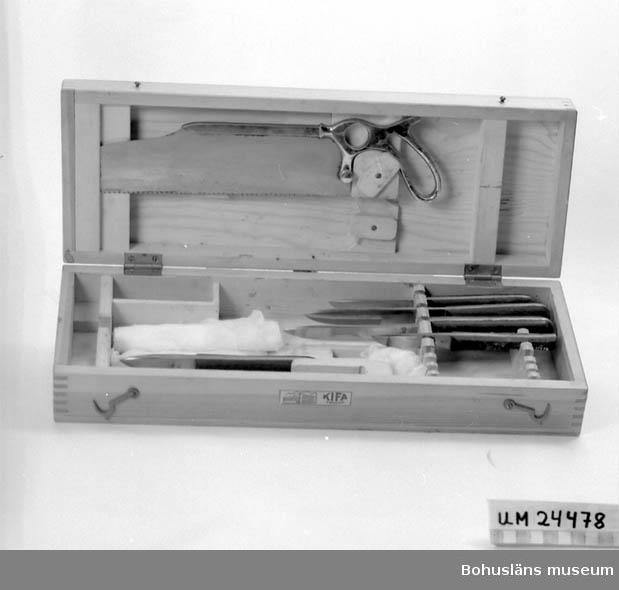 Trälåda innehållande: Fem knivar, en såg samt gasbinda. Verktyg ligger i fack som är specialgjorda för respektive verktyg.