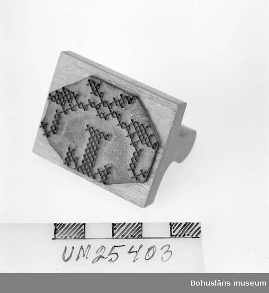 """594 Landskap BOHUSLÄN  Handtag av lövträ, figursågat och lackat. Undertill gummiplatta med  relief med ett """"T"""" (för Thorburn) och dekor i halvcirkel, allt för korsstygn. Stämplade färgförlaga på handdukar, lakan o. dyl. som skulle namnas. Ev. kvarsittande kalkerfärg gick bort i tvätten.  Det mesta  i linneförrådet skulle namnas och märkas. Personuppgifter om Ruth Thorburn se UM025358."""