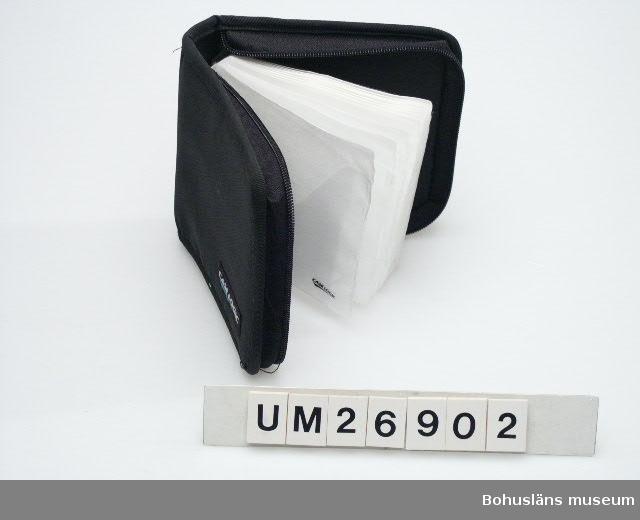 """410 Mått/Vikt TJ 4 CM Fodral för CD-skivor (skivor med inspelad musik i detta fall) i pärmliknande modell som stängs med blixtlås längs tre sidor. Omslag klätt med svart polyamid?tyg, grövre på utsian än insidan. På utsidan påsytt en tygetikett märkt: """"CASE LOGIC"""", samma märkning på blixtlåskläppen. Inuti finns 12 plastfickor för CD-skivor av genomskinlig plast med ett skyddsskikt av pappersliknande mjukt vitt filtat material med plastbaksida i varje plastficka. Några fläckar.  Insamlat i samband med en SAMDOK-dokumentation av båtturism.  För mer uppgifter om brukaren och dokumentationen se UM26869."""