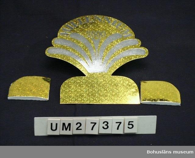"""Papp-palmett formad som ett stjärnfall, fontän eller en kaskad av guldglittrig papp med text i silver: """"MILLENNIUM 2000"""". För att kunna stå på bordet stagas palmetten med två självhäftande likaledes guldglittriga pappdelar med utvikbart dekorvikt rispapper som solfjäderformigt breds ut, en på varje sida.  Inköpt  i Uddevalla för 16:50.   För information om Millennieinsamlingen, se UM27360."""