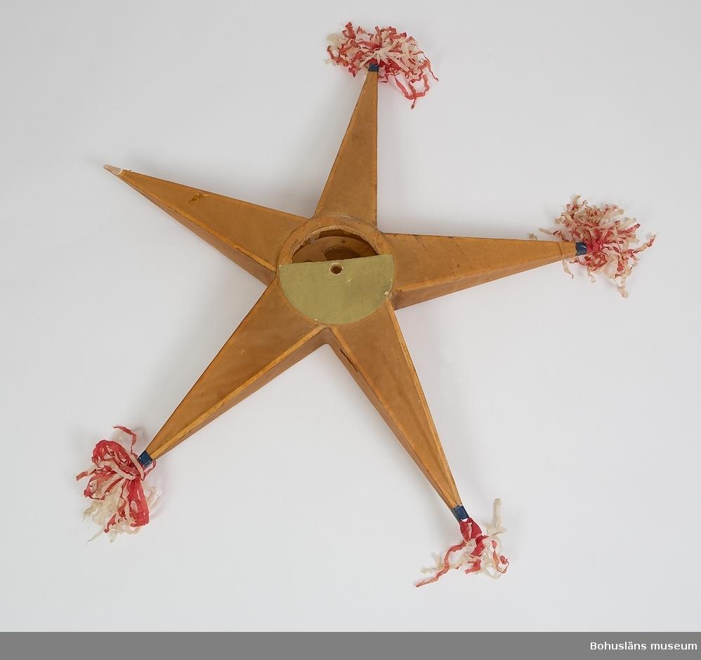 Stjärnan består av tunna, ohyvlade furupinnar, uppbyggda som armarna i en femuddig, tredimensionell stjärna runt ett nav, bestående av två ringar, grovt tillsågade eller skurna ur en rund platta där man sparat ut mittsektionen för ett borrat hål. Genom dessa hål har tidigare suttit den pinne runt vilken stjärnan kunnat snurras. Denna pinne har eventuellt avslutats med ett vevhandtag. Pinnen som stjärnan snurrat runt har i sin tur suttit i en längre tvärställd handtagsstång. Stjärnan har alltså kunnat snurras runt sin axel. Stommen är klädd med oljat eller vaxat, tunt, genomsiktigt papper. Navet är utvändigt dekorerat med tjock, guldfärgad papp, på framsidan klippt i samma form som navet, på baksidan en hel rund platta. Stjärnans framsida är på armarna dekorerade med utskurna, påklistrade bilder bestående av tre gröna ankare, två röda stjärnor, en grön stjärna och tre röda hjärtan, allt i papper. Stjärnans spetsar är klädda med röda och vita veckade tofsar av silkespapper, fastsatta med en grön pappersremsa. En av spetsarna saknar tofs. Pappershöljet är lagat på ett ställe och trasigt på fem ställen. Pappret är skört.