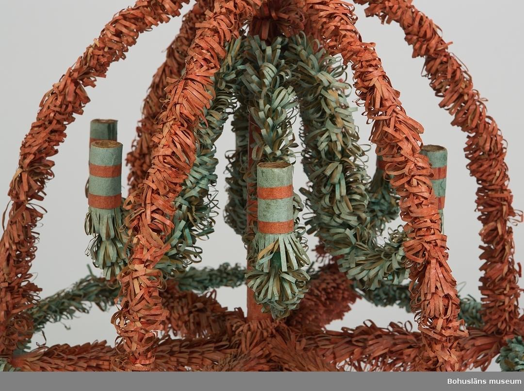 """Hög träljusstake av trä för sex ljus. Ljusstakens fot är tillverkad av en åttakantig mittdel, fastskruvad mitt i en korsformad underdel. Den åttkantiga mittdelen övergår i en rundsvarvad pinne, ca 40 cm hög. Runt denna pinne är själva krondelen konstruerad. I mötet mellan den åttkantiga och rundsvarvade mittståndaren börjar själva kronan som, underifrån räknat, består av ett """"hjul"""" med sex ekrar i vars ändar sitter runda, svarvade ljushållare, 30 mm i diameter, med hål lagom för kronljus, hållarna placerade utanför hjulets yttre krets. Strax innanför ljushållarna löper sex halvbågar, cirka 45 cm långa, som löper samman i kronans översta mitt. Cirka 10 cm ner på mittstången utgår sex nedhängande och nedtill uppböjda ljusarmar som avslutas med runda korkar, inklädda med kraftig papp, bildande ljushållare.  Dessa sex nedhängande armar liksom hjulets yttre krets och de sex halvbågarna är till verkade av grov metalltråd. Övrigt material är av trä. Ljusstakens fot är rödlackad. I övrigt är kronan klädd med dubbelvikt, vaxat grönt och rött glanspapper, klippt i täta fransar. Den svarvade mittdelen och ljushållarna är klädda med slätt glanspapper. Överst på kronan finns en tapp för påsättning av ytterligare en del, oklart vad, kanske ytterligare en ljushållare. Pappret är bleknat och kronan är smutsig."""