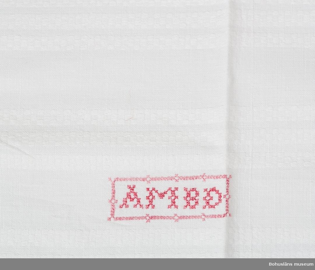 Handvävt lakan av bomull med påsydd virkad spets i ena kortänden, iknuten frans. Lakanet är ihopsytt av två våder. Mönstervävt i rutliknande randning som bildar ett reliefmönster. I ena änden två röda monogram broderade i korsstygn med bokstäverna AMBD inom ram.