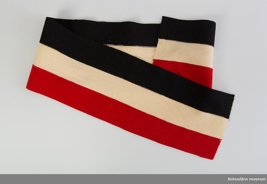 Ett band (bantlär?); långrandigt i rött, vitt och svart kläde. De olika färgade tygremsorna hopsydda med tät sicksacksöm på maskin. Inga fållar. Missfärgning ungefär mitt på remsan - det röda tyget som lätt blött på det vita. Två mindre hål i tyget i detta område samt en mörkare missfärgning. Del av riddräkt UM62.04.001 - UM62.04.007 Mer information se UM62.04.001