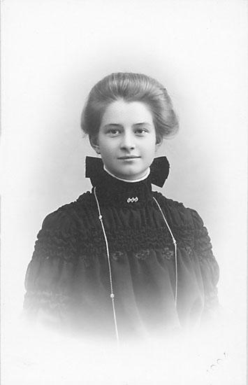 """Enligt noteringar: """"Till lilla Signe från vännen Sofia."""" Stämpel på framsidan: """"Falk, Karlshamn, Filial: Hoby."""" Inpräglar på fotot: """"1904."""""""