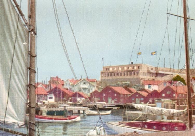 """Tryckt text på kortet: """"Gravarne. Hamnen och Hotell Kungshamn"""". Notering på kortet: """"Hamnstad omkr. 1950""""."""