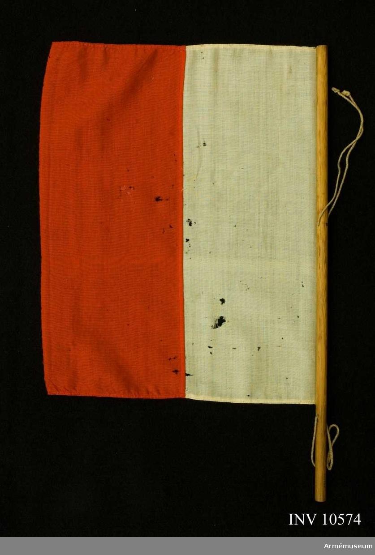 Grupp B I + H III. Duk av ylle i ett vitt och ett rött fält. Duken är spikad mot en smal stång.