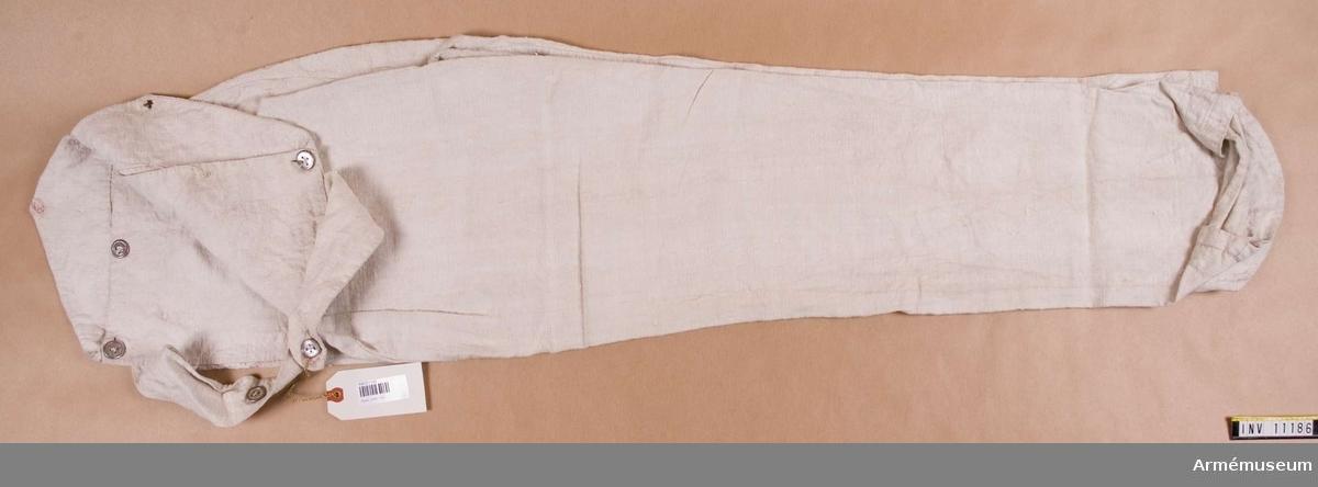 Grupp C I. Gåva från K.A.I.D. Byxorna i vitt linne, knäppes i midjan med två st tampar fastsydda i främre sidsömmen mitt bak med tennknappar i två avstånd (2 knappar, två knapphål). Bakstycket går upp i två flikar. En knapp på vardera. På vänstra flikens utsida står siffran 3 (2 cm hög). Framsidan knäppes med två knappar, en i varje sida. Mellan dessa tre knappar (1 saknas). Benets nedre framkant är något nedsvängd och byxan fästes under foten med påknäppbar hälla. Knapparna, två på varje insida av benet är av mindre storlek (13 mm) än de övre.