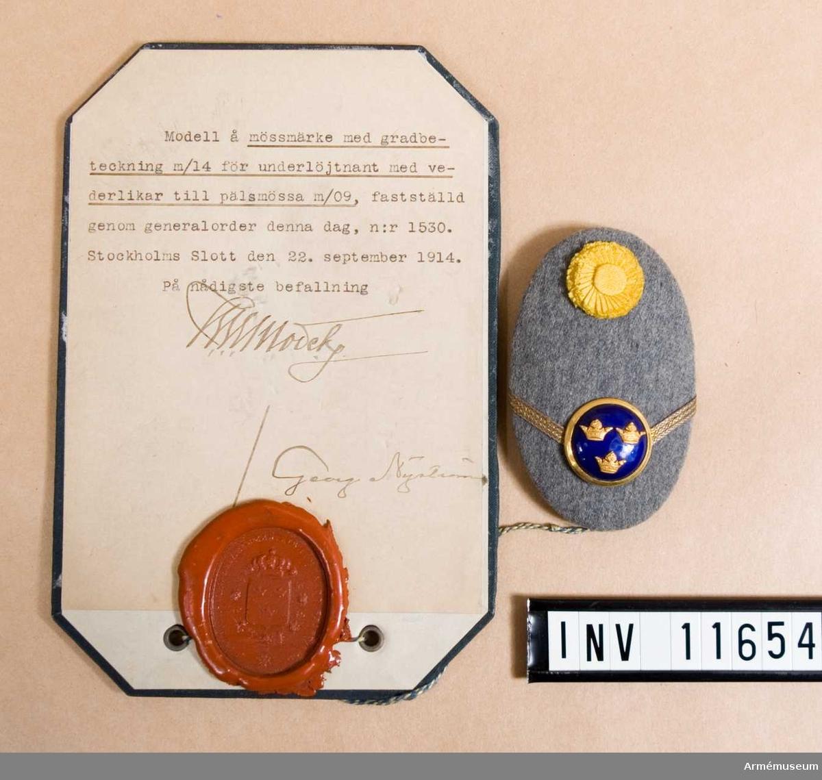 Grupp C I. Modell på mössmärke med gradbeteckning m/1914 för underlöjtnant med vederlikar till pälsmössa m/1909.  Dep från Arméförvaltningens Intendenturdep., modellkammaren.