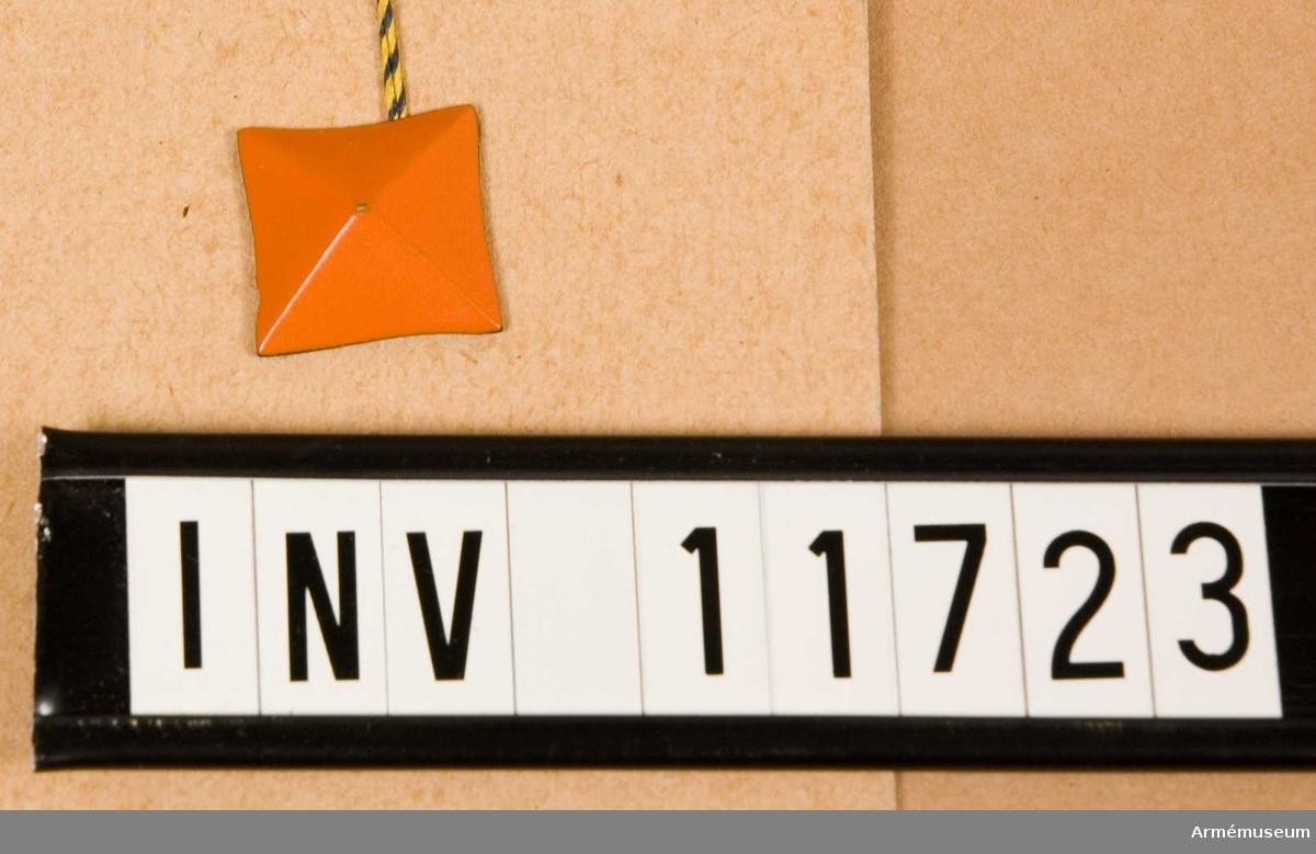 Grupp C I. Fyrkant m/1939, medelstor för civil personal, gradbeteckning, regementsofficer, orangegul. Förmodad gåva från Arméförvaltningens Intendenturavdelning, modellkammare.