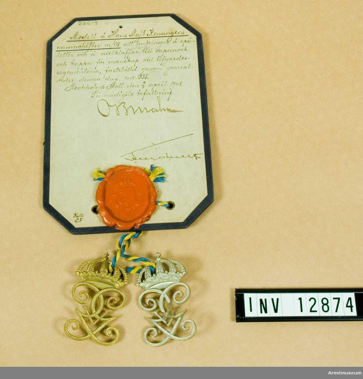 Grupp C I. Modell på Hans Majestät Konungens namnchiffer m/1908 att anbringas å epåletter och å axelklaffar till vapenrock och kappa för manskap vid Livgardesregementerna.  Deposition från Arméförvaltningens Intendenturdepartement, modellkammaren.