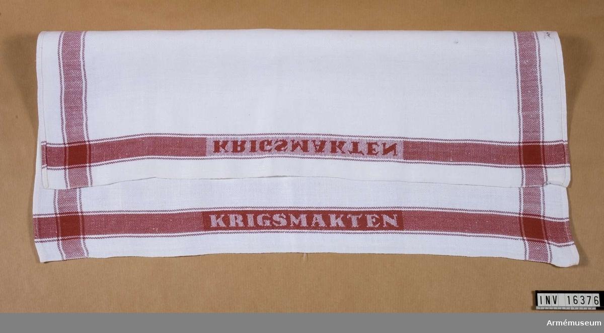 Samhörande nr är 16376-16379.Handduk.Handduk i halvlinne vävd i kypertteknik. Vit med röd bård runt om. På båda långsidorna i den röda bården är ordet KRIGSMAKTEN invävt.Handduken funnen i museet vid inventering av förråden 1987-07-28. Den är tillverkad före år 1975 då namnet Krigsmakten ändrades till Försvarsmakten.