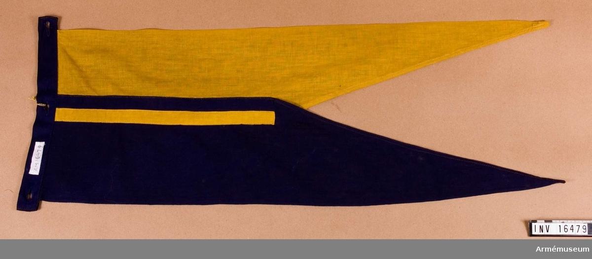 Tillverkad av blå och gul bomullsduk, så kallad flaggduk. Fästes på lans m/1851 med det blå partiet uppåt, överst.