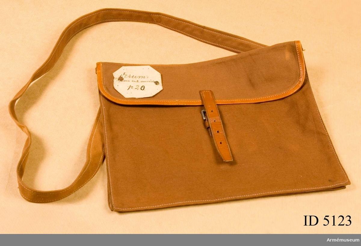 """Väsk för inkallelsebud. Textilväskan är platt och har ett djup av 20 mm. Väsklocket är läderskott och har en lädertamp som kan spännas i ett sölj- stycke fäst på väskans framsida. Från baksidan utgår en axel- rem också den i textil. På väsklockets vänstra hörn finns en en textilkett med texten """"Verums södra ink.område no.2"""".  Med väskan följer information: """"Fordomtida gick budkaveln genom våra bygderbudande allmogen till försvar yttre och inre fiender. Småningom utvecklades systemet till uppbåd men bibehöll alltjämt långt in i vår tid budkavlens idé. Teknikens språngartade utveckling inom kommunikationsväsendet har i ett slag revolutionerat förbindelsemedlen mellan myndighet och allmänhet. Nu i teleteknikens, bilens och flygplanets tidsålder sker uppbåd med andra medel. Denna väska för inkallelsebud fanns under 1900-talets första årtionden vid våra rullföringsområden. Den låg då färdigpackad med personliga  inkalleseorder till de vapenföra män, som vid ofred skulle  kallas till rikets försvar. Varje socken indela- des i två eller flera inkallelseområden. Särskilda personer voro vidtalade, att utan tövan föra budet vidare och utdela orderna. Kungörelser i kyrkor och genom anslag kompletterades mobiliseringsorderna. I nutiden vill denna lilla sak, minnas dels om den gamla sockenindelningen och dels om arvet från budkavlens dar. Orter inom socken är Emitslöv, Gryt, Färingtofta, Gilmåra, Hjärsås, Hästveda, Loshult, Mellby Strö, Oderljunga, Perstorp, Torup Örkened Vinslöv, Vittsjö, Visseltofta, Verum och Osby""""."""