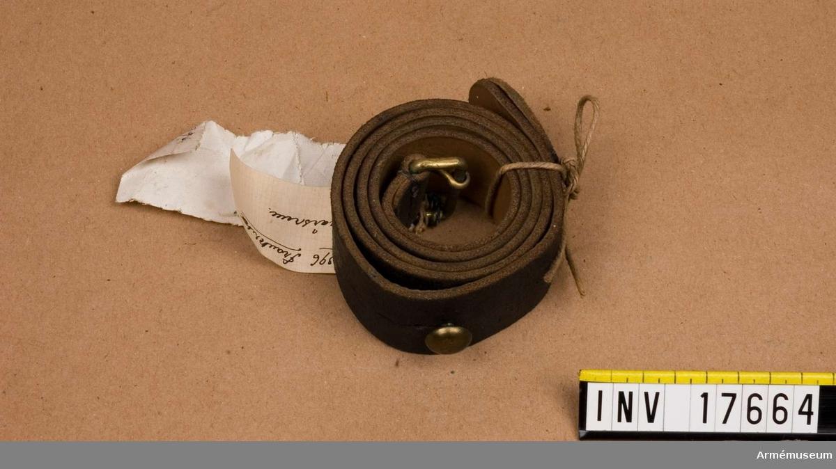"""Grupp E II Gevärsrem svartfärgad, 3.5 cm bred med spännen på ändan och en knapp på den andra, båda av koppar. På remmen finns stämplar med påskrift 1) """"E. Hemerdinger, Paris""""  2) """"26. 11. 1891""""."""