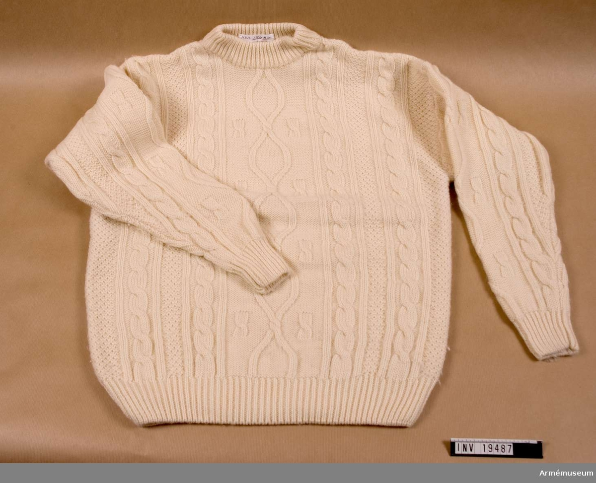 Tröjan är vit med flätstickning. Materialet är 100% ull. Tröjan har rund hals med resårstickning i hals mudd och midja.  Samhörande nr AM.19483-19494