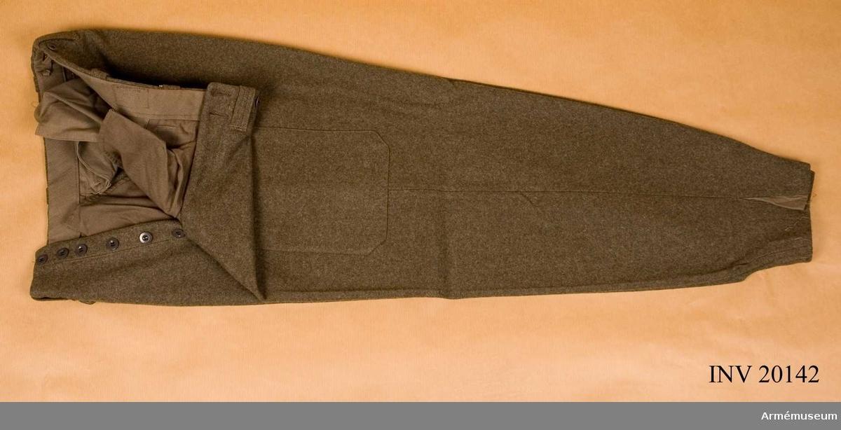 Långbyxor för utbildningschef. Grupp C I. Ur uniform för officer vid de i Sverige år 1939-45 utbildade danska och norska polistrupperna. Består av vapenrock, byxor, skjorta, slips, hjälm, vinterskor, damasker, livrem med pistol, silvakompass med fodral, kappa, handskar, halsduk och kartfodral. Av gröngrått kläde. Fickor -2 på sidan, 2 på bakbyxan, alla med lock som knäpps med knappar. På H byxben en påsydd liten ficka med lock och knapp, på V ben  en stor, fyrkantig ficka, också med lock och knapp. På frambyxan ett sprund med 6 benknappr och 6 likadana för hängslen. Foder av kakifärgat bomullstyg. Byxbenen smalnar mot nederkanten. LITT  Norske polititroppers uniformer og Distingsjoner 1945.  Statens reproduktionsanstalt 1945. Uniform för norska polis- trupper utbildade i Sverige. Album med uniformspersedlar med olika märken och gradkännetecken.