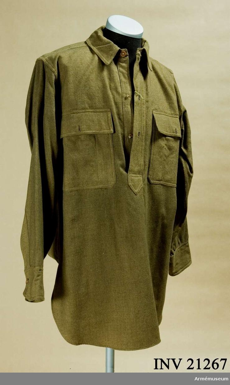 """Grupp C I. Skjorta av kakityg med tre kakibenknappar på bröstet. Fickor - två bröstfickor täckta med fyrkatiga ficklock försedda med en knapp. Krage, liggande, med foder av samma kakityg. Ärmuppslag, b:80 mm, med inskärning och en benknapp. I fickans inre sida finns en fastsydd etikett av tyg med påskriften: """"Phila. Depot, Q.M. Dept., U.S.Army"""". """"Inspected by"""". Med annat tryck finns följande påskrift: """"Philadelphia Depot May 24.1909. j. Sinon."""" LITT  Amerikanska uniformer ur """"Life"""" 19 may 1941. På 4:e sidan soldat med gevär (första i första raden) i samma skjorta. Enl Kapten Granberg."""