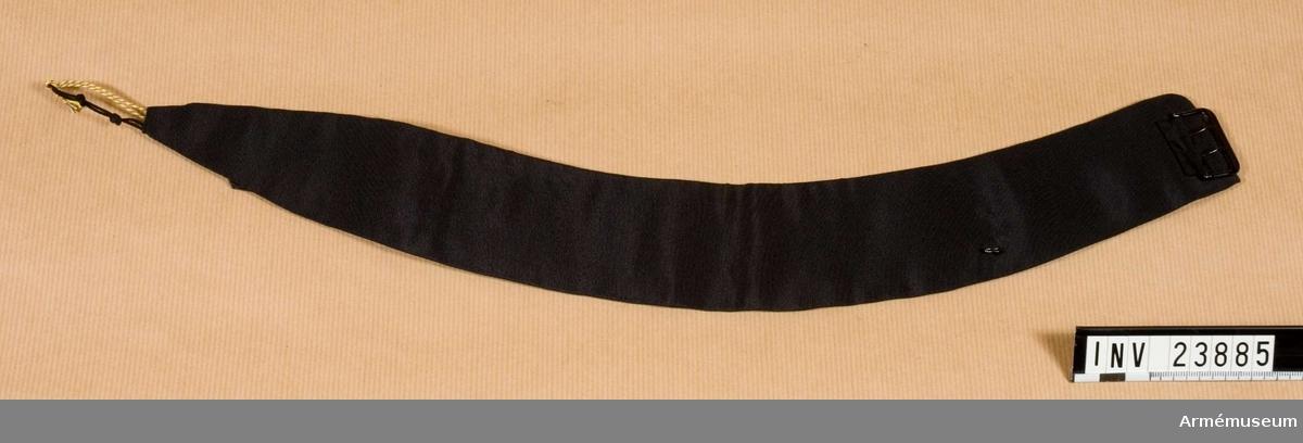 """Grupp C I. Av svart siden och med vitt foder. På en av ändarna finns ett svart spänne och på den andra en fastsydd tunga av svart satin med inskriften """"5 1/2/35"""" (ettan och tvåan delas med ett vågrätt streck med ettan överst)."""