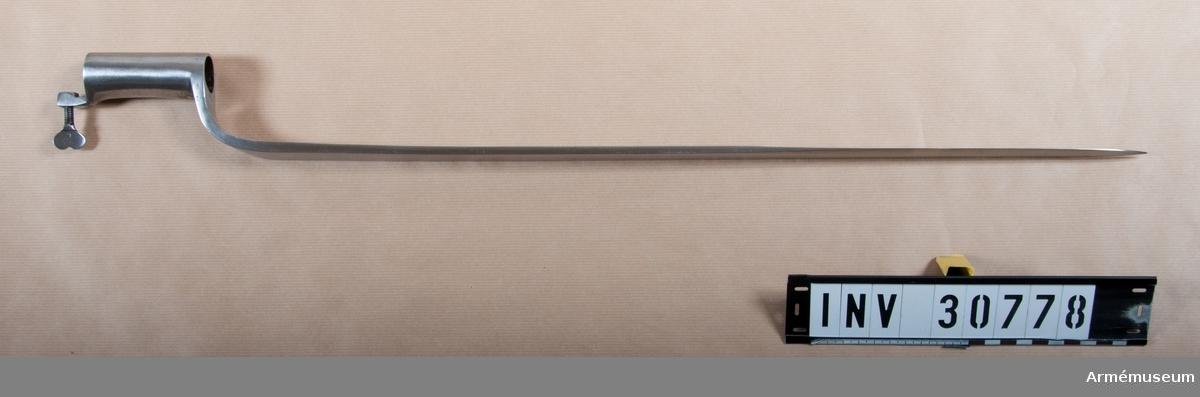 Grupp E II.  Bajonetthylsan är 8 cm lång och har nedtill på samma sida som bajonettarmen en med vingskruv försedd hållare. På armens insida finns ett skadat, dubbelt C och på klingans insida en egendomlig stämpel. På armens utsida är ingraverat N. 89. Klingan är eneggad med kilformigt tvärsnitt på större delen av sin längd, men omkr. 26 cm nedanför udden får den eggslipning även å ryggsidan. Nedtill är klingbredden 2,5 cm. Armen har rektangulärt tvärsnitt och samma bredd som klingan. Hållaren och hylsan är snidda ur samma stycke. J. Alm.