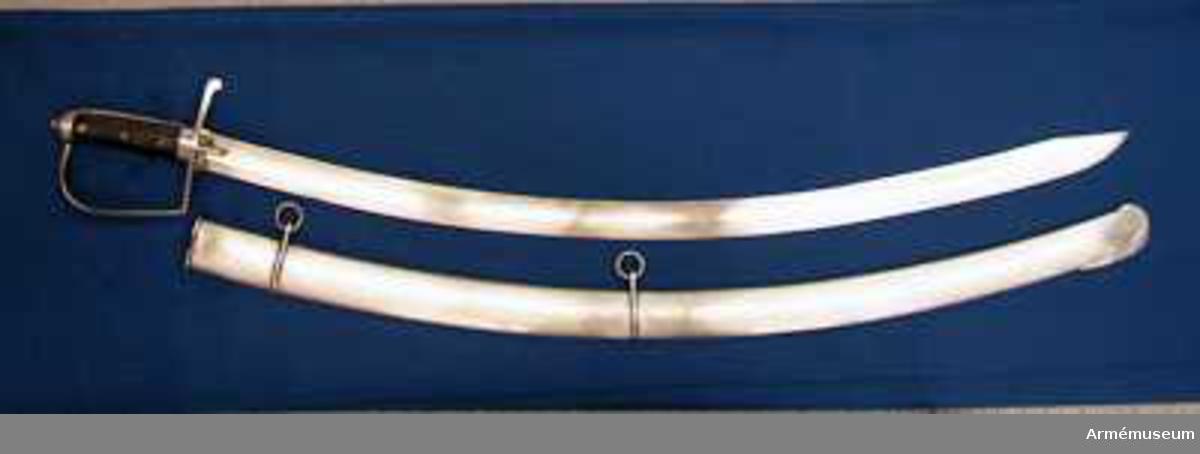 """Grupp D II.  Klingbredd upptill: 36 mm. Klingan är krökt samt på större delen av sin längd eneggad och skålslipad. Udden sitter nära nog i klingans mittlinje. På en längd av omkr 31 cm från udden har klingan egg även på rygg-sidan. Upptill på yttersidan står """"ZETTERBERG"""" och upptill på innersidan är en stämpel med bokstäverna C. F. K. inslagen.  Fästet är av järn. Tången är bred, och vid den är på var sida en skena av mörkt trä anbringad, vilka båda skenor fasthållas av tre genomgående nitar. Nederst omgives kaveln av ett ringliknande, 1,1 cm järnbeslag. Baktill har kaveln ryggbeslag, som uppåt övergår i en låg avrundad kappa. Tångens översta del fasthålles av en påskruvad, åttkantig liten mutter, som sitter ovanpå kappan. Parerstången är rak och har fyrsidigt tvärsnitt. Baktill avslutas den av en nedböjd knapp. Upptill på parerstångens bakre arm är siffran 8 inslagen. Ett par små styrskenor, som har avfasade kanter och avrundade ändar, utgår från undersidan av parerstångens mitt.Från parerstångens främre ände utgår hanbygeln i tvär vinkel men går ej rakt uppåt utan snett framåt. Den har på framsidan snedfasade kanter. Handbygelns övre ände är instucken under kappans främre kant.  Kallas i Modellsalens reversal """"Sablar med baljor, svenska, Hellvigs, st. 1"""". I Artillerimuseum kallades vapnet 1879-1884 """"Projekt till sabel med balja för Svenska kavalleriet, Generalfälttygmästaren Helvigs projekt, början av 1800-talet"""", men därefter ändrades benämningen till """"Sabel med balja m/1807 för svenska kavalleriet, generafälttygmästare Helvigs konstruktion"""". vilken benämning sidan sedan bibehölls."""