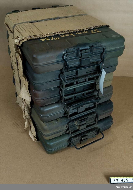 Grupp E X. Kanon med samhörande tillbehörslåda I och II; tolv  ammunitionslådor av plåt, fem dragtåg, rengöringsstång med  viskare i fodral, kikarsikte i träfodral, kikarsikte i  läderfodral, mynningsskydd, slutstyckskapell, presenning,  instruktionsbok.