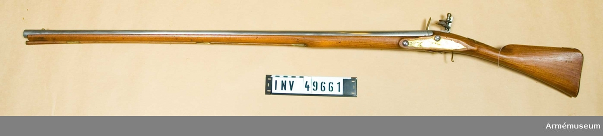 Grupp E XIV. Loppets relativa längd är 53 kal. Afrikanskt gevär med flintlås. Sidblecket består av en  mässingsskiva med gravyr föreställande båge med koger och  pilar. Varbygeln fattas. Barker.
