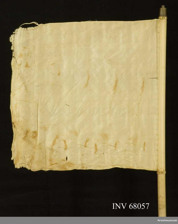 Duk: Tillverkad av vit sidentaft. Duken fäst vid stången med en rad tennlickor på mönstervävt band.  Dekor: Saknas.  Stång: Vitmålad, jämntjock. På 70 mm respektive 14 mm från nedre ändan mätt är läderremmar instuckna i stången, den övre formad till en 310 mm lång ögla, och den nedre bestående av en brun tamp, 540 mm lång.  Har holk.