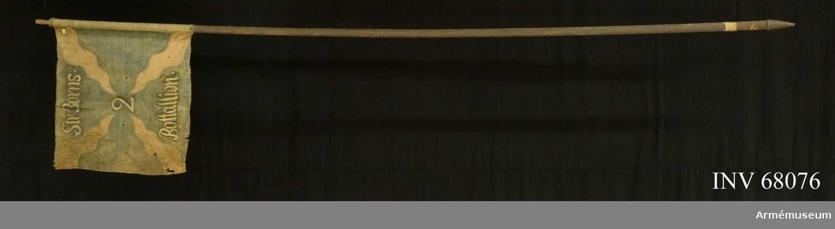 Duk: Tillverkad av enkel blå linnelärft. Från hörnen inåtgående flammor, i intarsia, i gult och i ett tätare vävt linne. Fäst vid stången med en rad mässingsspikar på ett blått linneband.  Dekor: Målad lika på båda sidor, text i vitt med mörk skuggning.  Stång: Tillverkad av mörkt blåmålad furu. Klack av järn. Trätapp för holk.