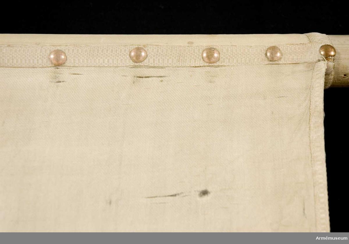 Duk: Tillverkad av enkel vit sidenkypert, sydd av tre horisontella våder. Fäst med en rad tennlickor på ett vitt band.  Dekor: Broderad omvänt lika på båda sidor Karl XIV Johans namnchiffer, dubbelt C bildat av små ornament, inom dessa XIV krönt av en sluten krona med vitt foder, liknande kronor ihörnen. Kantad med ett vitt band.  Stång: Tillverkad av vitmålad furu.