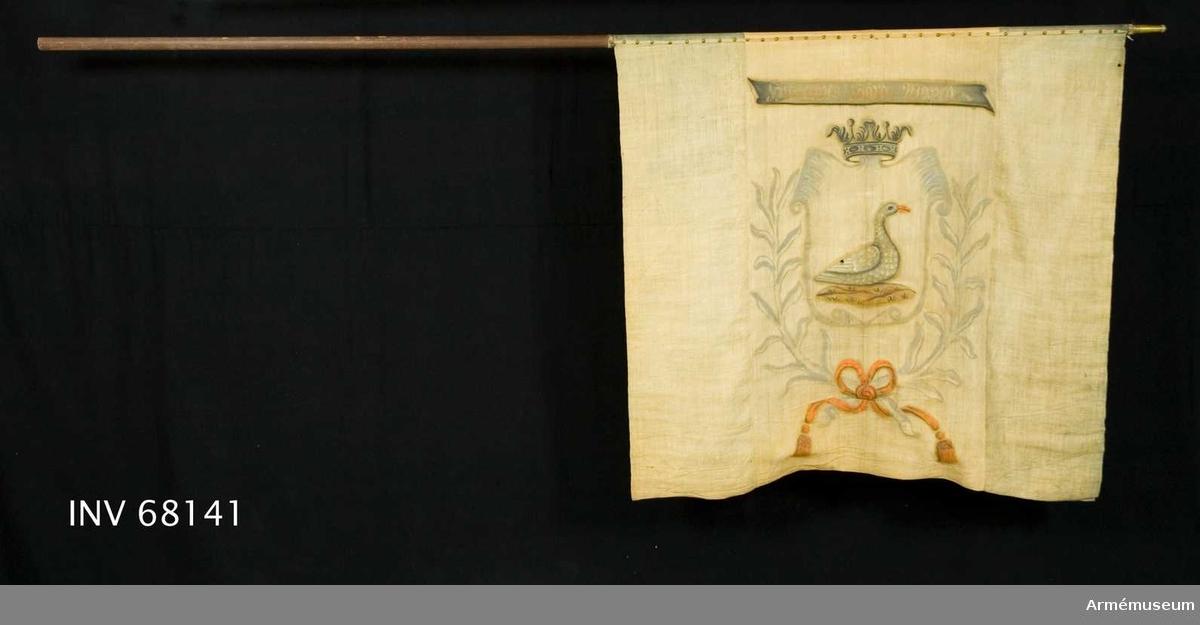 Duk: Tillverkad av enkel gul och blå linnelärft, blå fältet närmast spetsen. Fäst med en rad tännlikor på ett vitt kypertvävt band.  Dekor: Målad omvänt lika på båda sidor på det gula fältet. I den med öppen krona krönta skölden en grå gås med orangeröd näbb. Skölden innefattad av två kvistar, sammanknutna nedtill i rosett. Bandet i orangerött och med långa tofsprydda ändar. Över det hela ett grått språkband med text i gult på både in- och utsidan.  Stång: Tillverkad av brunmålat trä. Saknar spets. Holk av förgylld mässing.