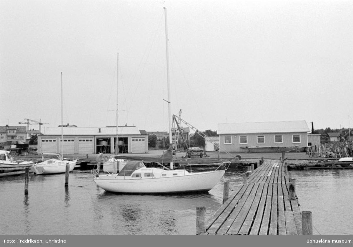 """Motivbeskrivning: """"Amigo varvet, Öckerö. På bilden syns till höger byggnad inköpt av Arne Arksund år 1966 (byggnaden arrenderades från 1962), till vänster i bild den senaste tillbyggnaden på varvet (se Bb 18:29)."""" Datum: 19800902 Riktning: Sv"""