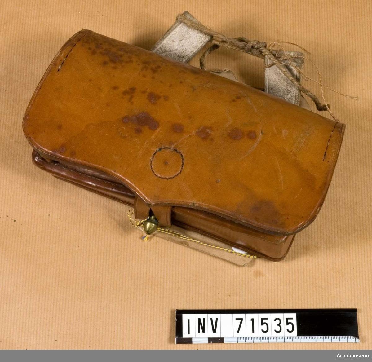 """Grupp C:II. Plats: Tyskland. Ammunitionsväska (""""Munitionstasche"""") i form  av infanteripatronväska av brunt läder (utom två fastsydda löpare) och består av: Lock som stänger väskan med en läderbit och som har knapphål på baksidan med en stämpel där det står: """"August Loh"""" """"Hoflieferant Militair - Effecter. Fabrikant. Berlin"""". Väska rymmande tio nästen för pistolpatroner (pistolen infördes för ridande menig vid fältartilleriet år 1864). På väskans framsida två fickor för tolv knallhattar och skruvmejsel; en ficka stänges med läderknapp och den andra med ett lädersnöre, på väskans undersida en kopparknapp att stänga väskan med. På väskans baksida två fastsydda öglor av älghud att fästa väskan vid livremmen.  Litteratur: Enl. Geschichte der Bekleidung und Ausrüstung der König. Preus. Armée in den Jahren 1808 bis 1878. Berlin 1878. Sid: 241 § 1109: Efter en dagorder av den 6. maj 1864 fingo ridande menig vid fältartilleriet pistoler, ammunitionsväska för tio patroner, tolv knallhattar och skruvmejsel efter modell av infanteriväskan. Ammunitionsväskan har en kartongetikett med texten. Für Munition, für Artillerie v. 6/5 1864. Enligt Kapten W.Granberg."""
