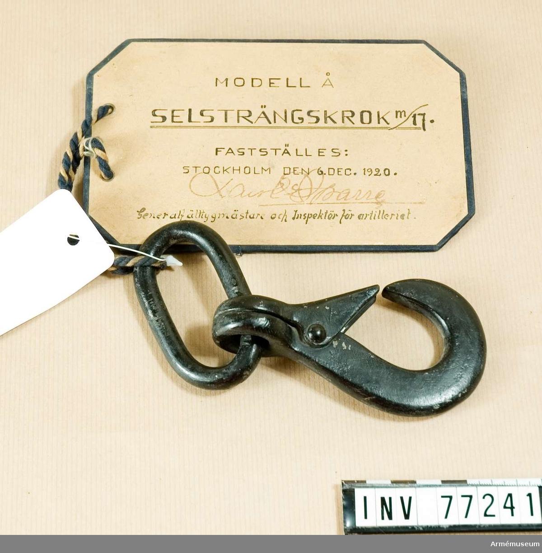 """Grupp K II. Selsträngskroken är försedd med en modellapp med texten: """"Modell å Selsträngskrok m/17 fastställes. Stockholm den 6. december 1920 Sparre Generalfälttygmästare och Inspektör för artilleriet""""."""