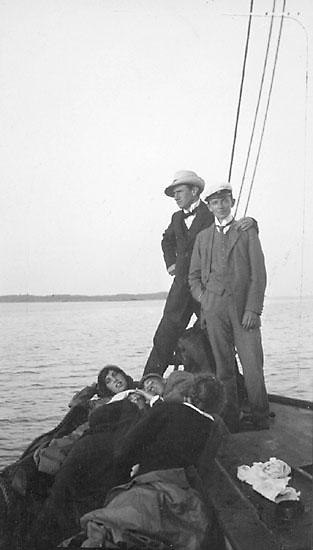 Ett sällskap på en båt, några ligger på däck, två män står upp, den ena med armen om den andra